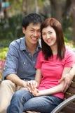 Νέα κινεζική χαλάρωση ζεύγους στον πάγκο πάρκων Στοκ Εικόνα