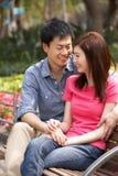 Νέα κινεζική χαλάρωση ζεύγους στον πάγκο πάρκων Στοκ Φωτογραφία