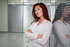 Νέα κοκκινομάλλης επιχειρηματίας στο διάδρομο του γραφείου που εξετάζει τη κάμερα στοκ φωτογραφία