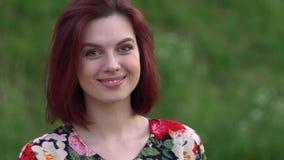 Νέα κοκκινομάλλη μάτια και χαμόγελο γυναικών ανοικτά που εξετάζουν τη κάμερα φιλμ μικρού μήκους