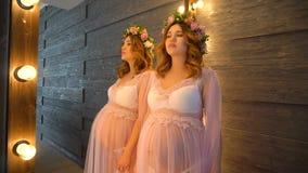 Νέα κομψή έγκυος γυναίκα που στέκεται κοντά στον καθρέφτη φιλμ μικρού μήκους