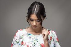 Νέα κομψή γυναίκα με το κουλούρι hairstyle σχετικά με την κλειδαριά τρίχας που κοιτάζει κάτω Στοκ Φωτογραφία