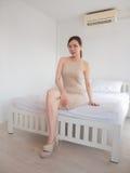 Νέα κομψή συνεδρίαση γυναικών σε ένα κρεβάτι στοκ φωτογραφία με δικαίωμα ελεύθερης χρήσης