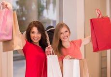 Νέα κορίτσια με τις τσάντες αγορών στο κατάστημα Στοκ φωτογραφία με δικαίωμα ελεύθερης χρήσης