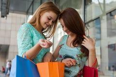 Νέα κορίτσια που ανοίγουν τις τσάντες αγορών τους Εποχή των πωλήσεων Στοκ Εικόνες