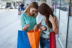 Νέα κορίτσια που ανοίγουν τις τσάντες αγορών τους Εποχή των πωλήσεων Στοκ εικόνες με δικαίωμα ελεύθερης χρήσης