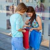Νέα κορίτσια που ανοίγουν τις τσάντες αγορών τους Εποχή των πωλήσεων Στοκ Εικόνα
