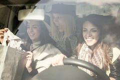 Νέα κορίτσια που επιστρέφουν από τις αγορές Νέα κορίτσια που οδηγούν το αυτοκίνητο στοκ εικόνες