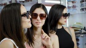 Νέα κορίτσια που θέτουν στα γυαλιά ηλίου μπροστά από το φακό καμερών απόθεμα βίντεο