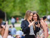Νέα κορίτσια που θαυμάζουν τις φωτογραφίες πήραν το mirorrless έκκεντρο Στοκ Εικόνα