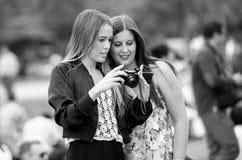 Νέα κορίτσια που θαυμάζουν τις φωτογραφίες πήραν το mirorrless έκκεντρο Στοκ Εικόνες