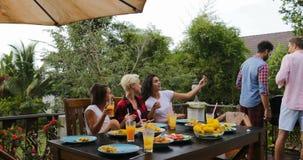 Νέα κορίτσια που κάθονται στον πίνακα που παίρνει selfie τη φωτογραφία ενώ τα άτομα ομαδοποιούν τους μαγειρεύοντας φίλους σχαρών  απόθεμα βίντεο