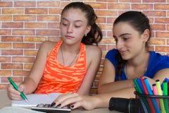 Νέα κορίτσια που κάθονται στο γραφείο στο σπίτι Δύο κορίτσια που κάθονται στο γραφείο στο σπίτι, που κάνει την εργασία Στοκ Φωτογραφίες