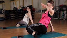 Νέα κορίτσια που κάνουν τις ασκήσεις στο χαλί για τη γιόγκα Η έννοια ενός υγιούς τρόπου ζωής και του αθλητισμού Σειρά ασκήσεων φιλμ μικρού μήκους