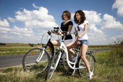 Νέα κορίτσια που οδηγούν ένα ποδήλατο Στοκ Φωτογραφίες
