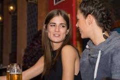 Νέα κορίτσια που πίνουν και που έχουν τη διασκέδαση από κοινού Στοκ Εικόνες