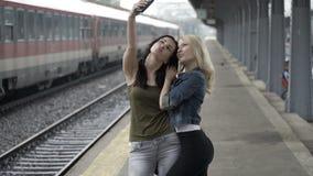 Νέα κορίτσια που φθάνουν και που συναντιούνται στο σταθμό τρένου και που παίρνουν τις εικόνες ενός selfie με το smartphone απόθεμα βίντεο