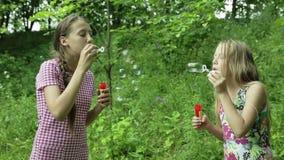 Νέα κορίτσια που φυσούν τις φυσαλίδες σαπουνιών υπαίθριες φιλμ μικρού μήκους