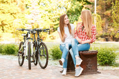 Νέα κορίτσια που χαλαρώνουν μετά από την οδήγηση ποδηλάτων Στοκ Φωτογραφία