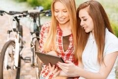 Νέα κορίτσια που χαλαρώνουν μετά από την οδήγηση ποδηλάτων Στοκ εικόνα με δικαίωμα ελεύθερης χρήσης