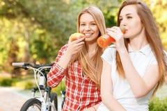 Νέα κορίτσια που χαλαρώνουν μετά από την οδήγηση ποδηλάτων Στοκ Εικόνες