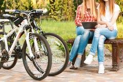 Νέα κορίτσια που χαλαρώνουν μετά από την οδήγηση ποδηλάτων Στοκ φωτογραφία με δικαίωμα ελεύθερης χρήσης