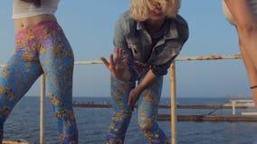 Νέα κορίτσια που χορεύουν στην αποβάθρα θαλασσίως φιλμ μικρού μήκους