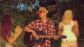 Νέα κορίτσια που χορεύουν στους ήχους κιθάρων στο πάρκο αργά απόθεμα βίντεο