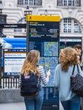 Νέα κορίτσια που ψάχνουν για τις κατευθύνσεις σε έναν χάρτη του Λονδίνου στοκ εικόνες