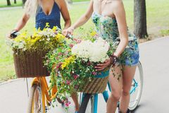 Νέα κορίτσια στα ποδήλατα με τα λουλούδια Στοκ Εικόνες