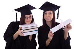 Νέα κορίτσια στο μανδύα σπουδαστών με το δίπλωμα και τα βιβλία Στοκ φωτογραφία με δικαίωμα ελεύθερης χρήσης