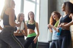 Νέα κορίτσια sportswear που κουβεντιάζουν πριν από τη χορεύοντας κατηγορία στοκ φωτογραφία