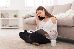 Νέα κουρασμένη γυναίκα που διαβάζει ένα βιβλίο Στοκ Εικόνες