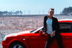 Νέα κυρία γοητείας στα γυαλιά ηλίου καθρεφτών που εξετάζει τη κάμερα κοντά σε ένα κόκκινο αθλητικό αυτοκίνητο Στοκ Φωτογραφίες