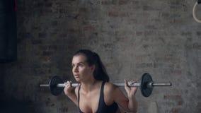 Νέα κυρία μαύρο sportswear που κάνει τις στάσεις οκλαδόν με το barbell Έννοια δύναμης και κινήτρου φιλμ μικρού μήκους