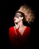 Νέα κυρία με μια φυσώντας τρίχα σε ένα κόκκινο φόρεμα στοκ εικόνες
