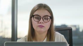 Νέα κυρία με τα γυαλιά που εξετάζει το lap-top στοκ εικόνα με δικαίωμα ελεύθερης χρήσης