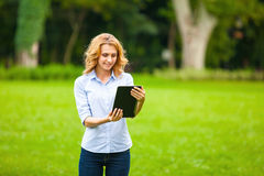 Νέα κυρία με την ταμπλέτα στο πάρκο Στοκ εικόνα με δικαίωμα ελεύθερης χρήσης