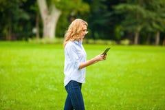 Νέα κυρία με την ταμπλέτα στο πάρκο Στοκ Φωτογραφία