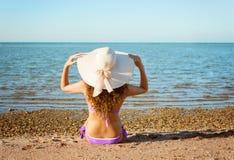 Νέα κυρία με τη σγουρή συνεδρίαση τρίχας και καπέλων στην άμμο Στοκ Φωτογραφίες