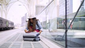Νέα κυρία με τις αποσκευές κοντά στο σιδηροδρομικό σταθμό φιλμ μικρού μήκους