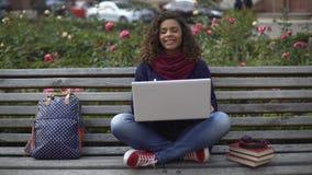 Νέα κυρία με το ειλικρινές χαμόγελο που κουβεντιάζει on-line με τους φίλους, ελεύθερος χρόνος απόθεμα βίντεο