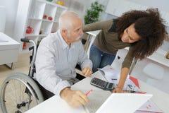 Νέα κυρία που βοηθά συνδεδεμένο το αναπηρική καρέκλα άτομο στον υπολογιστή χρήσης Στοκ εικόνα με δικαίωμα ελεύθερης χρήσης