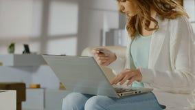 Νέα κυρία που ελέγχει την ισορροπία στον τραπεζικό λογαριασμό που χρησιμοποιεί το lap-top, κάρτα απόθεμα βίντεο