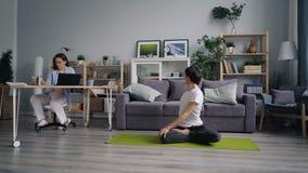 Νέα κυρία που εργάζεται με τον υπολογιστή ενώ φίλος που κάνει την αθλητική γιόγκα στο εσωτερικό απόθεμα βίντεο