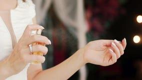 Νέα κυρία που εφαρμόζει το άρωμα πολυτέλειας στον καρπό και τη μυρωδιά της, που επιλέγουν το παρόν κίνηση αργή κλείστε επάνω φιλμ μικρού μήκους