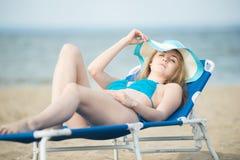 Νέα κυρία που κάνει ηλιοθεραπεία σε μια παραλία Όμορφη τοποθέτηση γυναικών Στοκ Φωτογραφία