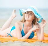 Νέα κυρία που κάνει ηλιοθεραπεία σε μια παραλία Όμορφη τοποθέτηση γυναικών Στοκ Εικόνα