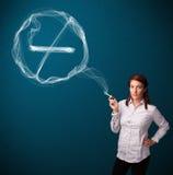 Νέα κυρία που καπνίζει το ανθυγειινό τσιγάρο με το σημάδι απαγόρευσης του καπνίσματος Στοκ φωτογραφίες με δικαίωμα ελεύθερης χρήσης