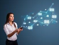 Νέα κυρία που κρατά ένα τηλέφωνο με τα βέλη και τα εικονίδια μηνυμάτων Στοκ εικόνα με δικαίωμα ελεύθερης χρήσης
